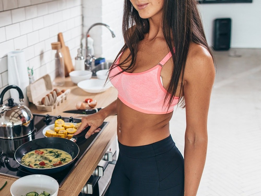 Female athlete cooking breakfast
